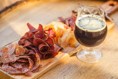 Stout and jerky. Glass of dark stout beer served with lean meat snacks on a wooden barrel Stock Images