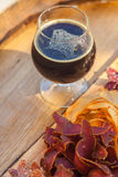 Stout and jerky. Glass of dark stout beer served with lean meat snacks on a wooden barrel Royalty Free Stock Photo