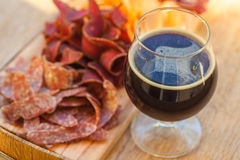 Stout and jerky. Glass of dark stout beer served with lean meat snacks on a wooden barrel Royalty Free Stock Photography
