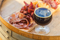 Stout and jerky. Glass of dark stout beer served with lean meat snacks on a wooden barrel Stock Photos