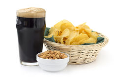 Stout with peanuts and chips. Close up of stout with peanuts and chips Royalty Free Stock Images