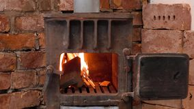 Stove on background of rough brickwork. In country house in the mountains, burning firewood in stove with the open door stock video