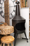 Stove and furnishing. Shop interior with wooden furniture and metal stove Stock Photo