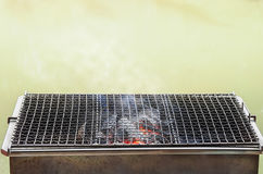 Stove. With grate for BBQ grill on blurred light background Royalty Free Stock Image