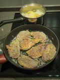 On the stove, preparing a dinner of chops and potatoes Royalty Free Stock Photo