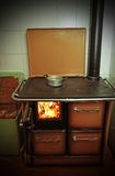 Stove a wood-burning Stove with fire lit in the old mountain hom Stock Image