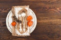 Stoviglie con il Physalis e l'argenteria arancio Fotografie Stock Libere da Diritti