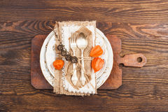 Stoviglie con il Physalis e l'argenteria arancio Fotografie Stock