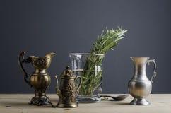 Stoviglie d'annata con il vaso ed i rosmarini di vetro sulla tavola di legno Fotografia Stock Libera da Diritti