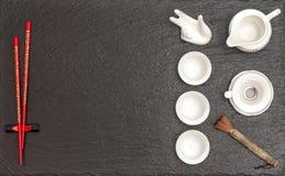Stoviglie per cerimonia di tè asiatica Teiera, tazze e bastoncino rosso Fotografie Stock Libere da Diritti
