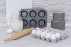 Stoviglie per la cottura, la muffa del dolce ed il vassoio con le uova sulla tavola in grande cucina leggera Fotografie Stock Libere da Diritti