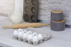 Stoviglie per la cottura, la muffa del dolce ed il vassoio con le uova sulla tavola in grande cucina leggera Fotografie Stock