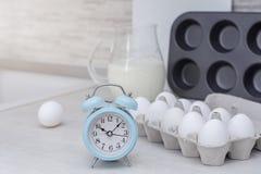 Stoviglie per la cottura, la muffa del dolce ed il vassoio con le uova sulla tavola in grande cucina leggera Fotografia Stock Libera da Diritti