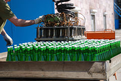 Stowage of wine bottles with autoloader. Green wine bottles are stowed with autoloader on sunlit autotruck. Accumulator car is in winery yard Royalty Free Stock Image
