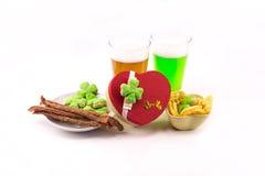 StPatrick ` s天以心脏的形式庆祝礼物啤酒与开胃菜香肠芯片和三叶草的贮藏啤酒绿色两块玻璃  免版税库存照片
