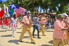 StPatricks musikbandet för dagmarschen ståtar på stranden, Cabarete, Dominikanska republiken Royaltyfria Foton