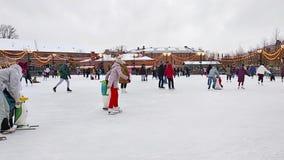 StPetersburg Ryssland - 01 Januari 2019: En folkmassa av folk som åker skridskor på isisbanan på ferierna för nytt år Barn lär at arkivfilmer