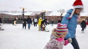 StPetersburg Ryssland - 01 Januari 2019: En folkmassa av folk som åker skridskor på isisbanan på ferierna för nytt år Barn lär at lager videofilmer