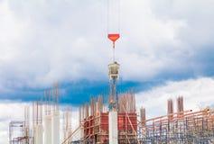 Sträcka på halsen den lyftande behållaren och arbetaren för konkret blandare i arbetsplats för konstruktionsbyggnadsplats på himm Arkivbild