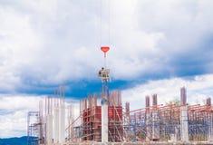 Sträcka på halsen den lyftande behållaren och arbetaren för konkret blandare i arbetsplats för konstruktionsbyggnadsplats på himm Royaltyfri Bild