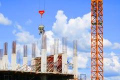 Sträcka på halsen den lyftande behållaren och arbetaren för konkret blandare i arbetsplats för konstruktionsbyggnadsplats på himm Royaltyfri Foto