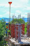 Sträcka på halsen den lyftande behållaren och arbetaren för konkret blandare i konstruktionsbyggnadsreklamfilm i platsarbetsplats Royaltyfria Foton