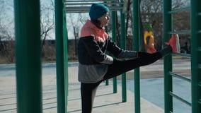 Sträcker den caucasian kvinnan för pannaskottet utomhus på sportjordstänger i vinter stock video