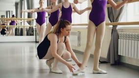 Sträcker flitiga studenter för gulliga flickor av balettskolan praktiserande grundläggande positioner för ben, medan deras instru arkivfilmer