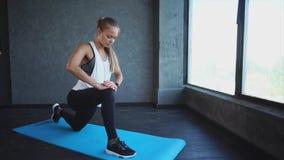 sträckning Älskvärd ung kvinna som gör ben som sträcker i konditionstudion stock video