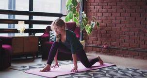 Sträckning av kroppen i den unga damen för morgonen hon gör hemma som yoga, poserar på det mattt i vardagsrum med modern design o lager videofilmer