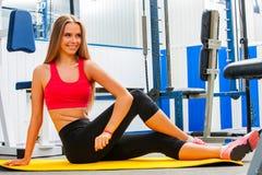 Sträckning av kvinnan i sportidrottshall Vridning av att öva för flicka Fotografering för Bildbyråer