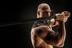Sträng barbar i läderdräkt med svärdet Royaltyfri Bild