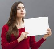 Sträng 20-talflicka med långt brunt hår som rymmer ett meddelande på vit bakgrund Arkivfoto