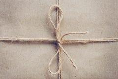 Stränga eller tvinna bundet i en pilbåge på brun textur för kraft papper royaltyfria bilder