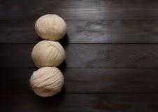 Stränge des weißen Garns sind auf einem dunklen Holztisch Stockfoto