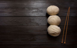 Stränge und hölzerne Stricknadeln auf einem braunen Holztisch Stockfotos