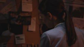 Strävsam trött kvinnlig utredare som försöker att finna ledtråd till röverilösningen lager videofilmer