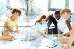 Strävsamma kollegor som sitter i kontoret som täckas med legitimationshandlingar Royaltyfri Fotografi