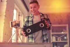 Stråla den upphetsade tonåringen som visar modern musikalisk utrustning arkivfoton