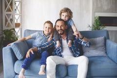 Stråla farsan som lokaliserar med pojkar på soffan arkivfoton