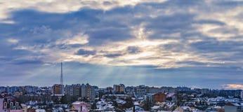 Strålar av de dramatiska molnen för sol över staden Royaltyfri Foto
