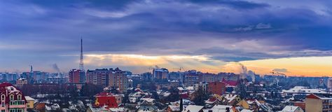 Strålar av de dramatiska molnen för sol över staden Arkivfoto