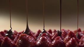 Strålar av glasyr hälls långsamt på blasten av jordgubbebär arkivfilmer