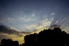 Strålar av inställningssolen till och med molnen Arkivfoton