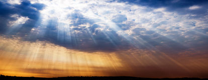 Strålar av ljus som skiner in i staden, dramatisk solnedgång Royaltyfri Bild