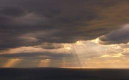 Strålar av ljus under solnedgång över havet royaltyfri foto