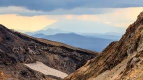 Strålar av solen gör deras väg till och med molnen Solnedgång på den Mutnovsky vulkan, Kamchatka halvö, Ryssland royaltyfri foto