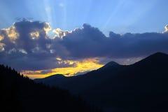 Strålar av solen som gör deras väg till och med molnen mot bakgrunden av maxima av bergen royaltyfri foto