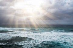 Strålar av solljus bryter till och med stormmoln ovanför det öppna havet Fotografering för Bildbyråer