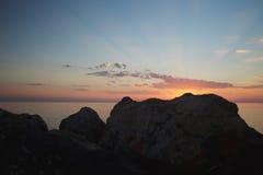 Strålar av solnedgången bland stenarna Arkivfoto